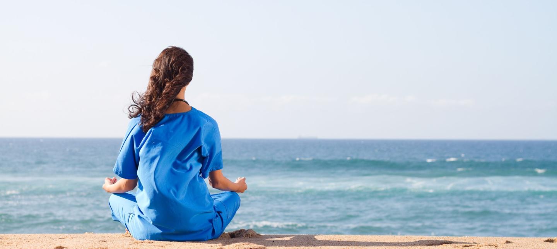 A female nurse sitting on a beach looking at the sea.